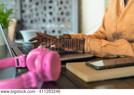 African Woman Working On Laptop In Bar Restaurant - Side View Afro Female Hands Typing On Computer -