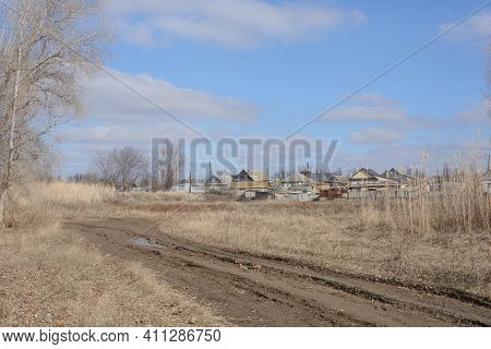 Outskirts Of Village In Early Spring. Dirty Road, Beautiful Sky And Houses. Rural Landscape.