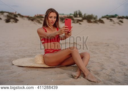 Beautiful Woman In Bikini With Straw Hat Sit And Makes Selfie At Sandy Beach.
