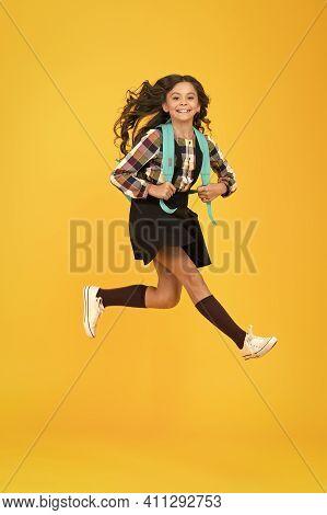 Childhood Activity. Happy Child In Midair Yellow Background. Little Kid Back To School. Childhood De