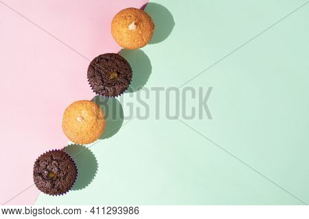 Row Of Chocolate And Vanilla Muffins On A Plate On A Pink And Turquoise Background With Crumbs, Geom