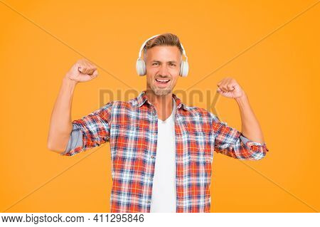 Happy Man Flex Strong Arms Listening To Music In Modern Headphones Yellow Background, Sound Power.