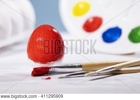 Painting Easter Eggs, Preparation For Spring Holiday, Red Egg With Palette Of Colors On Blue Backgro
