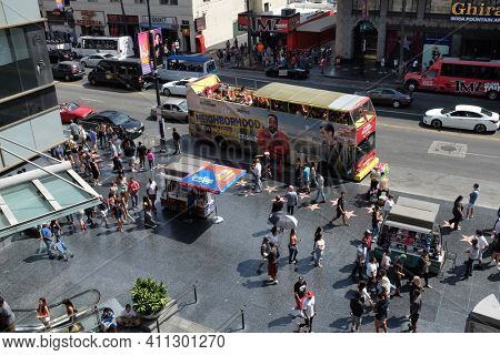 HOLLYWOOD - SEPT 2, 2018: Hollywood Blvd with tourists and tour busses and the Walk of Fame at the Hollywood and Highland Center.