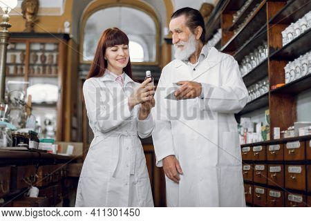 Two Pharmacists, Senior Man And Young Woman Working In Vintage Old Drugstore. Male And Female Pharma