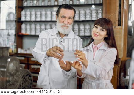 Handsome Senior Bearded Caucasian Man Pharmacist And His Young Female Colleague, Posing In Vintage O