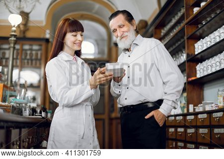 Professional High-skilled Young Female Pharmacist Talking With Senior Man Client While Showing Him T