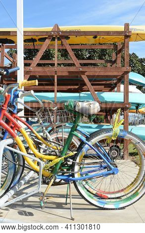 DANA POINT, CA - NOVEMBER 14, 2016: Colorful bicycles in a bike stand with a kayak rack in the background in Dana Point Harbor, California.