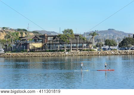 DANA POINT, CA - NOVEMBER 4, 2016: Dana Point Yacht Club with paddle boarders passing in front.