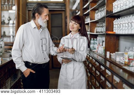Professional Young Woman Pharmacist Talking With A Handsome Senior Male Client While Showing Him The