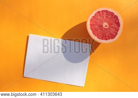 Summer Still Life With Half Of Grapefruit And Blank Paper Card On Orange Background. Invitation Mock