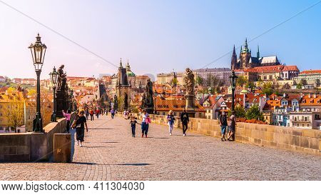 Prague, Czech Republic - April 17, 2020: People With Face Masks Walking On Charles Bridge In Prague.