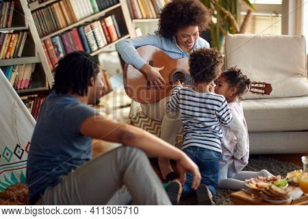 Kids are interested in the guitar played by their Mom in a relaxed atmosphere at home. Family, together, love, playtime