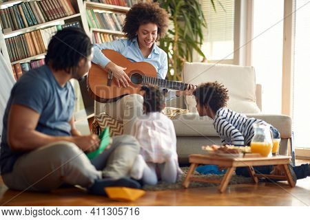 A happy mother who plays the guitar for her family in a cheerful atmosphere at home. Family, together, love, playtime