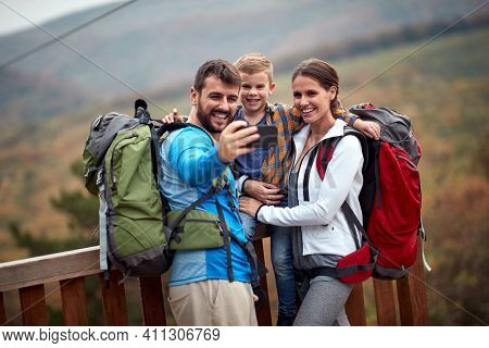 Cheerful young hiker family making selfie outdoor