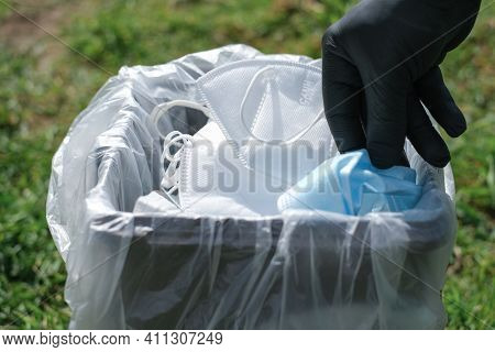 Man Hand While Trash Protective Mask On Separate Garbage Bin, Covid19 Medical Disposal Waste