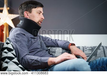 Man Employee After Accident Working At Home Behind Laptop And Feels Pain In Neck, Uses Black Neck Co