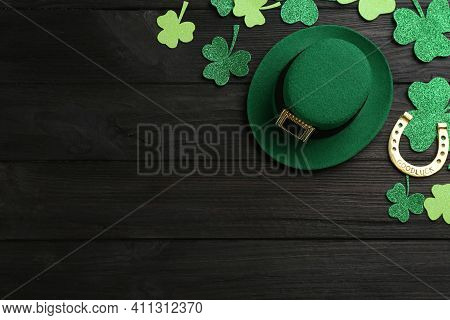 Leprechaun's Hat And St. Patrick's Day Decor On Black Wooden Background, Flat Lay. Space For Text