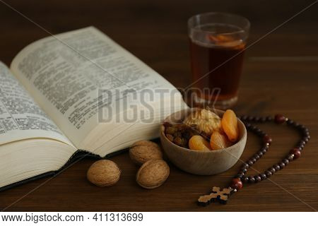 Bible, Rosary Beads, Walnuts And Dried Fruits On Wooden Table. Lent Season