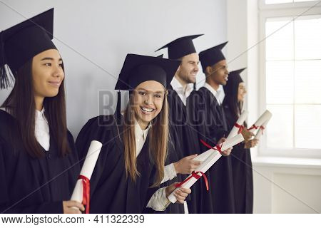 Woman With A Diploma In Hand Stands In A Row Near His Multiethnic Classmates Friends Near The Wall.