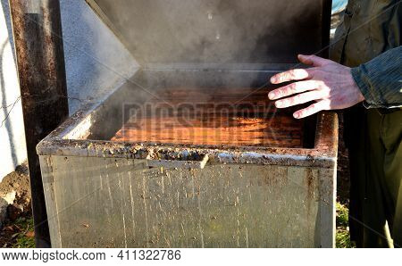 Work Of A Beekeeping Company Melting Old Dark Wax Combs. In A Stainless Steel Steam Boiler. The Wax