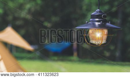Illuminated Vintage Hanging Black Camping Lantern With Blurred Background Of Field Tents In Camping