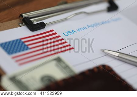 Ballpoint Pen And Dollar Bills Lying On Documents For Applying For Visa Closeup. Assistance In Filli