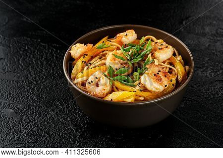 Wok Egg Noodles With Shrimps, Yellow Pepper And Sesame Seeds In A Dark Brown Plate On A Black Backgr
