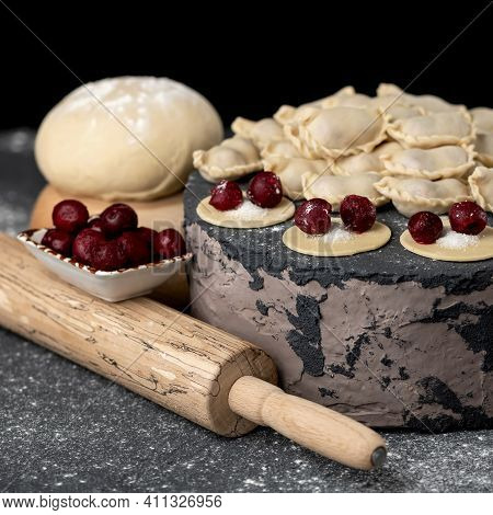 Sweet Cherry Filling On Raw Dough Circles. Delicious Still Life With Rolling Pin On The Table. Proce