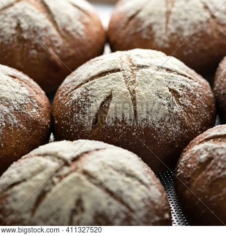 Whole Loaves Of Dark Bread In Rows. Bread Background. Close Up. Fresh Baked Whole Grain Bread. Selec