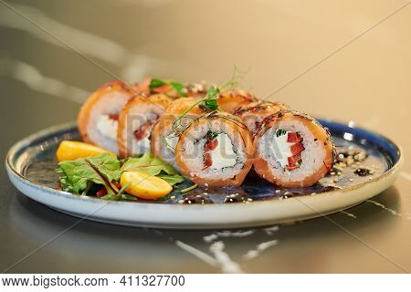 A Close-up Photo Of Fresh Sushi Rolls With Salmon, Philadelphia Cheese, And Tuna On A Blue Ceramic P