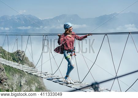 A Happy Cheerful Woman Walks On A Suspension Bridge High In The Mountains. Wanderlust And Adventures