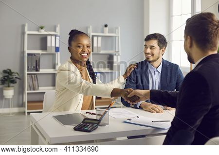Happy Young Interracial Couple Shake Hand Of Male Bank Manager Broker