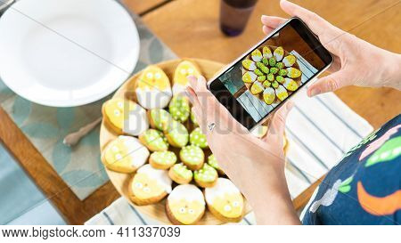 Food Blogger Photographs Food On A Smartphone. An Internet Influencer Takes Pictures Of Iced Sugar C