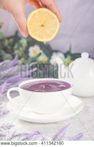 A Woman's Hand Squeezes A Lemon Into A Mug Of Purple Tea. Lemon Juice Drips Into A Mug.