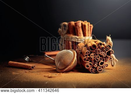 Ground Cinnamon, Cinnamon Sticks, Tied With Jute Rope On A Black Reflective Background. Copy Space.