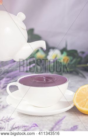 Purple Tea From A White Teapot Is Poured Into A White Mug. On Top Of A White Table Among The Flowers