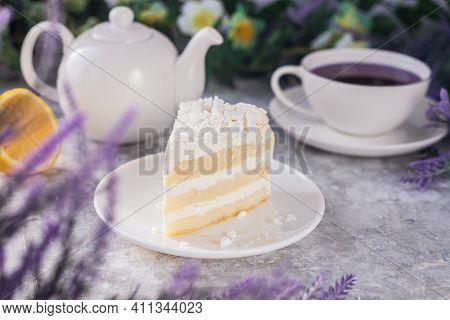 Cut Off A Piece Of Cake With White Cream On The Table Next To A Mug And Kettle And Lavender Flowers.