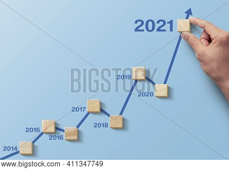 Wooden Blocks Arranged In An Increasing Graph With The Word 2021 On Blue Background. Business Growth