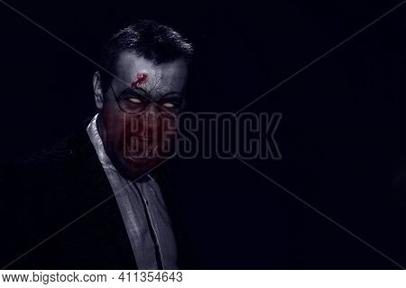 Horror Scene Of A Man With Bloody Face. Zombie In Jacket And Glasses. Toned Image. Horror Concept