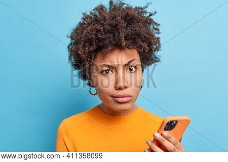 Discontent Afro American Woman Smirks Face Looks With Dissatisfied Expression Holds Modern Cellular