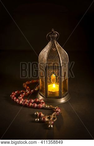 Beautiful Egyptian lantern and misbah. Glowing ramadan lamp on dark background. Metal Ramadan light and prayer beads.