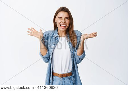 Cheerful Smiling Woman Shrugging Shoulders As If Know Nothing And Winking At Camera, Feeling Silly,