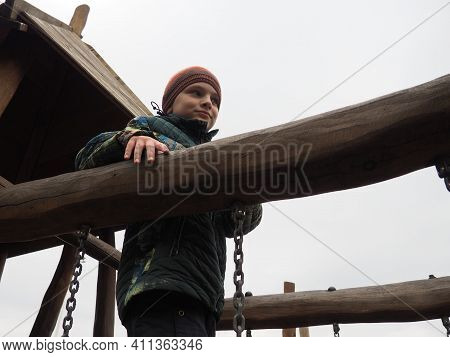 Boy 8 Years Old On The Playground. The Child Is Dressed In Warm, Demi-season Clothes - A Brown Hat A
