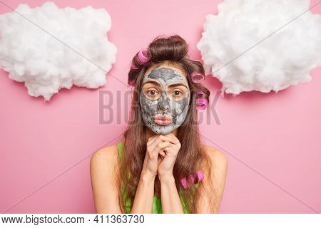 Beautiful Brunette Woman Keeps Hands Under Chin Applies Hair Curlers For Making Hairstyle Clay Mask