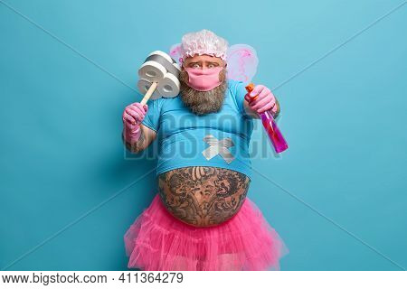Funny Bearded Man With Fat Tattooed Belly Wears Fairy Costume Protective Mask Holds Detergent And Pl