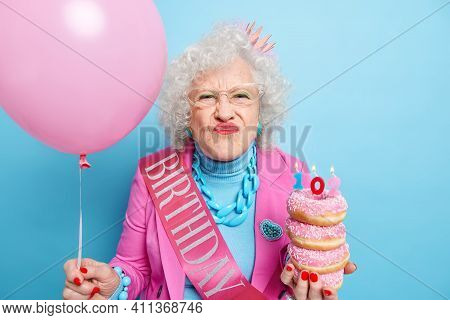 Portrait Of Funny Wrinkled Woman Makes Frimace Pouts Lips At Camera Holds Pile Of Tasty Doughnuts In