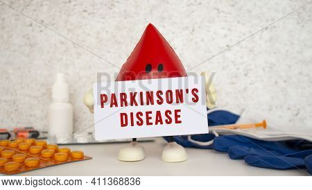 A Toy Drop Of Blood Holds A White Paper Card With The Inscription Parkinsons Disease. Medical Concep