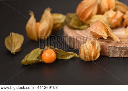 Ripe Berry Physalis On The Wooden Board.