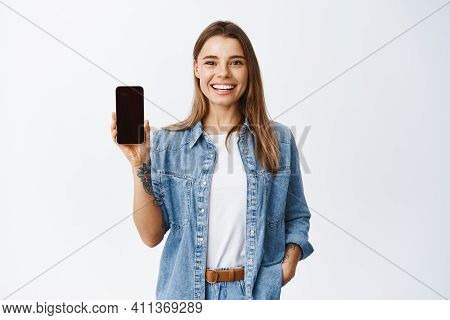 Portrait Of Attractive Young Woman With White Smile, Showing Empty Smartphone Screen, Demonstrate An